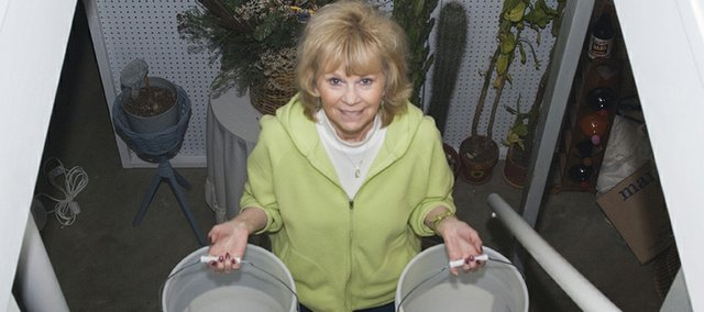 Barb Cranor holds up two of the five-gallon buckets she uses to collect excess water from her air conditioner.
