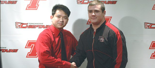 Dana College wrestling coach Beau Vest shakes hands with the program's latest recruit, Tonganoxie High senior Cameron Adcox, who signed with DC on April 8 at THS.