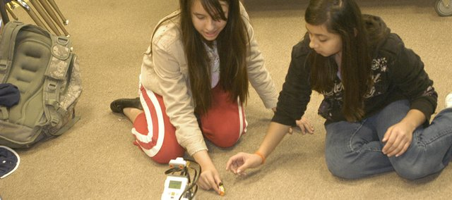 Fifth-graders Joselin Deleon and Veronica Juarez test their Lego robot by putting a Lego man in its path. The students stay after school programming robots as part of Starside Elementary School's Lego Robotics club.