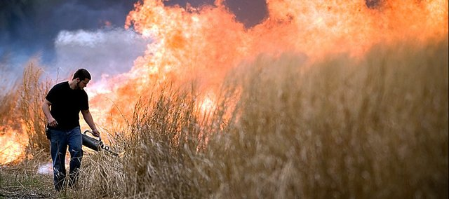 Baker University junior Kyle Ruona, Baldwin City, makes his way through the Baker Wetlands, igniting the tall grass during a controlled burn Thursday. The ash carbon produced by the fire helps many plants by acting as a natural fertilizer.