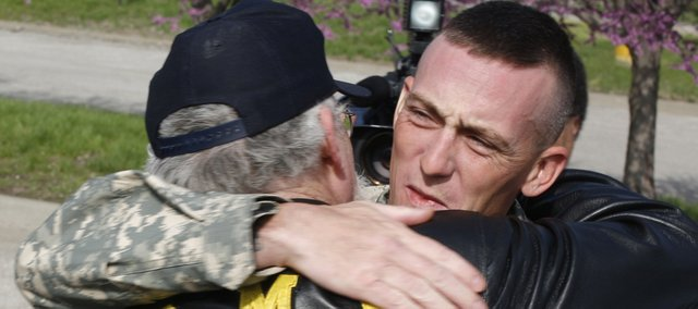 US Army Sgt. Joe Peel, center, of Tonganoxie, is greeted by his father, Eddy Peel, of Tonganoxie, and other Patriot Guard members Friday, April 25, 2008 during a stop in Lawrence on Peel's way back to Tonganoxie. Peel returned to Kansas on April 21 after serving a tour in Iraq. The Patriot Guard surprised him with a motorcycle escort from Lawrence to Tonganoxie.