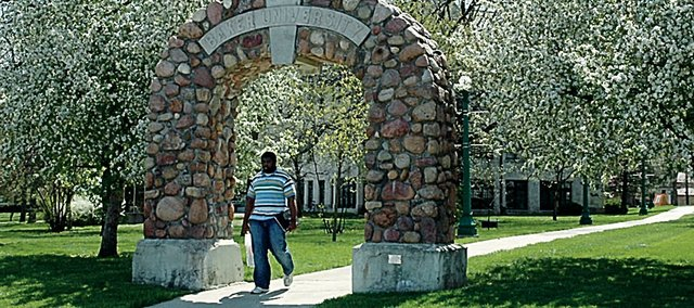Tim Obiefule, a junior at Baker University from Lawrence, passes through the memorial arch on campus amidst the spring-time blooms of flowering trees. Baker has been awarded a $450,000 grant to improve science instruction in middle schools.