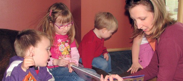 Stacey Kite  (right) reads a book to Jerek Rexroat, 2, Natalie Kite, 3, Blake Kite, 1 and Angelina Barnett, 4, Monday afternoon in the children&#39;s area of the new Basehor Community Library. The library opened Monday morning to the public at its new location, 1400 N. 158th St.