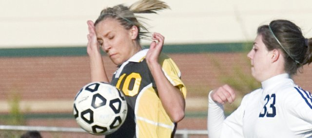Basehor-Linwood senior Audrey Brock (10) tries to avoid hand contact on the ball as well as the attack from Mill Valley's Kaitlyn Stacy Tuesday. Both teams remained scoreless in the first half but Mill Valley came around to defeat Basehor 3-0.