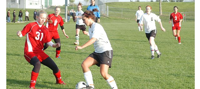 De Soto midfielder Kelsey Fisher tries to keep possession of the ball as a Shawnee Heights player attempts a tackle. The Wildcats lost to the Thunderbirds, 5-0, Monday night.