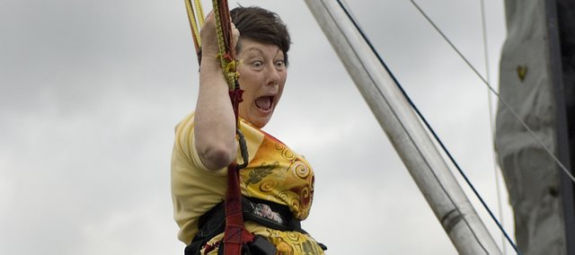 Vickie Hughes, family and consumer science teacher,  tries out the bungee equipment at Tonganoxie Middle School Thursday. TMS students and teachers were celebrating the preliminary Kansas Assessment Test data, which showed marked improvements over last year&#39;s test.