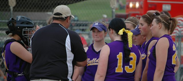 McLouth High softball players listen as coach Ballard Patterson goes over defensive strategy during a tight contest with Silver Lake that was eventually suspended in the 10th inning with the scored tied, 4-4.