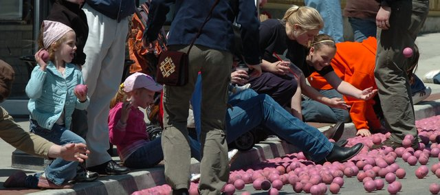 Spectators try to stay clear of the Pinkie balls that raced down Oak Street Saturday.