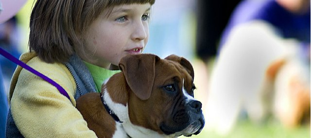 Rilee Garner, 7, and her four-month-old boxer named Zoe, await their turn for the Tonganoxie Recreation Commission&#39;s best-dressed dog competition at Chieftain Park Saturday. The boxer was presented to a group of judges wearing nothing else, but a pair of plaid boxer shorts. The competition was part of the Rec Commissions summer kick-off party.