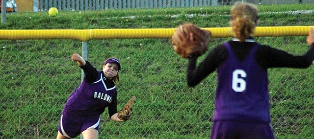 Baldwin High School freshman Morgan Burton, left, throws a ball to junior Tracie Weege from deep left field. Gardner recorded a single on the play, but lost the doubleheader to the Bulldogs.