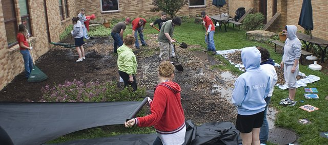 Tonganoxie High School students lay out tarp and remove rocks from the outdoor classroom at the Tonganoxie Elementary School Friday. All of the THS students went throughout town and participated in the first ever Community Service Day.