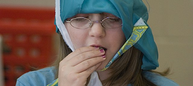 Sixth-grader Katie Kelsey tries a bit of a biscuit during medieval day at Tonganoxie Middle School.
