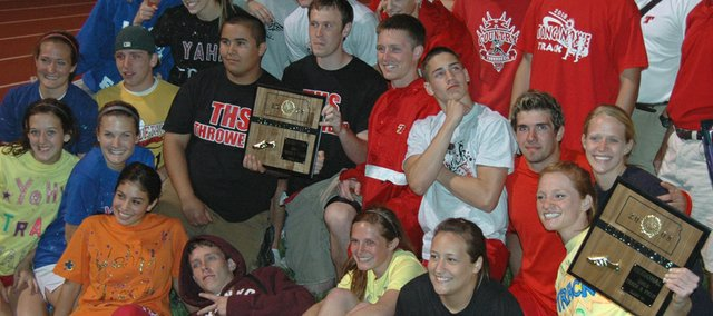 Tonganoxie High track and field athletes and coaches celebrate after the girls and boys teams won regional chapmionships on Friday at Wamego.