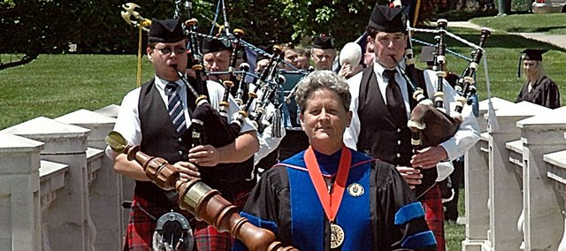 Karen Exon, Baker University faculty member, leads the processional across the Taft Bridge on Baker University's campus Sunday before the commencement ceremony.