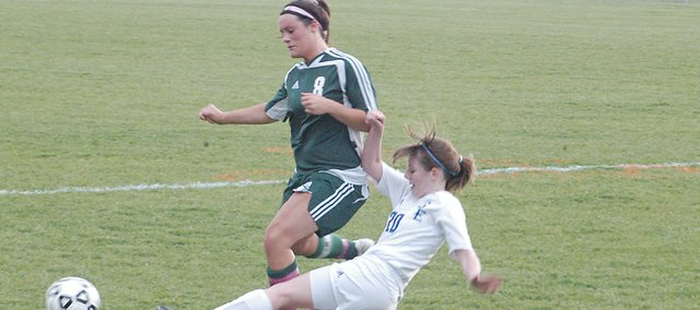 Julie Bray tries to maintain possession of the ball while a Gardner Edgerton player slides in for the tackle. De Soto beat Gardner May 13, but lost to St. Thomas Aquinas May 16, ending the Wildcats' season.