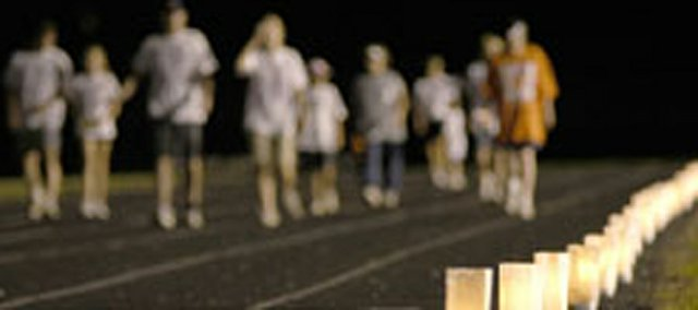 Luminaries along the track glow as walkers make their way around