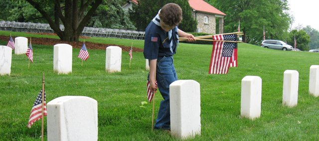 Mark VanEyck, 6, a Cub Scout with Olathe Cub Scout Pack 3777, erects an American flag in front of a headstone at the Leavenworth National Cemetery Saturday. Boy Scouts and Cub Scouts from Leavenworth and surrounding counties laid roughly 30,000 flags in preparation for Monday's Memorial Day ceremony.