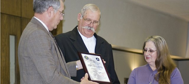 Willard Harper, FAA representative from the Kansas City International Airport, left, presents Larry Turpin, and his wife Jeanne Turpin, with the 2008 Charles E. Taylor Master Mechanic Award Thursday. Turpin was nominated for the award after completing 50 years in the aviation industry as an accredited mechanic.