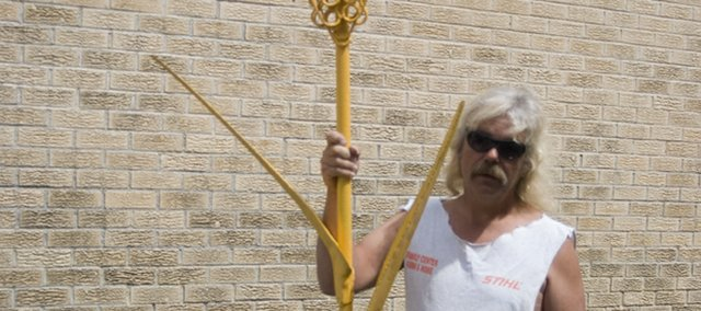 Local chainsaw artist Russ Ehart, displays his latest work, an 8 1/2 foot tall metal sculpture of a wheat stalk May 20. Ehart, who is used to working with wood, said it took him about a week to finish the sculpture because he had to buy a lot of new tools so he could work with the new medium. The sculpture is for Stanley Itzen of Hillsboro. Another project Ehart has been working on is a chainsaw carvers competition that will be held at the Leavenworth County Fairgrounds and will be a part of Tonganoxie Days. Ehart said he has about six carvers that are ready to participate. He has invited the carvers to bring pieces to sell and has arranged for all of the pieces made during the competition to be sold at an auction that will begin at 4 p.m. the same day.