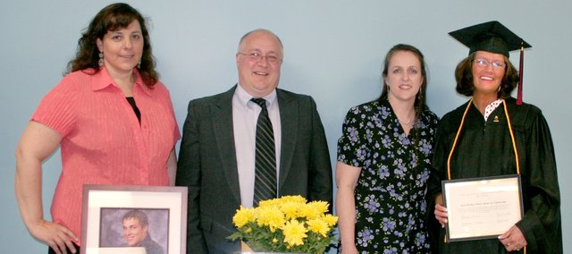 From left, Lisa Lowman, Lansing Educational Achievement Program coordinator,  Richard Moore, Marlene Moore and LEAP graduate Judy Settles stand behind the display honoring the Moores' late son, Jared, after the LEAP graduation ceremony May 16. Settles was selected as the first Jared Michael Moore Scholarship.