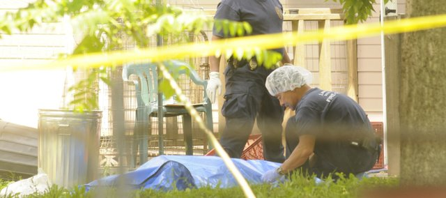 A Lawrence-Douglas County Fire and Medical worker and a Lawrence Police Officer tend to the body of a deceased male who was pronounced dead at the scene of a shooting at 1311 Delaware.  Two men were reported dead at the scene.