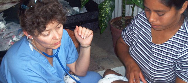 Dr. LeAnne DeTar Newbert checks out a baby during a 2002 medical mission in Venezuela. DeTar Newbert and  her mother, Margaret Stephens, both of Bonner Springs, will be departing next week for a two-week medical mission to a rural area near Mombasa, Kenya.