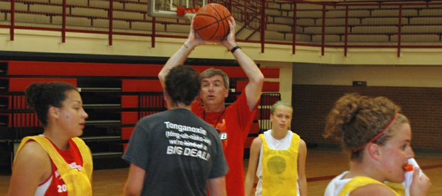 Tonganoxie High coach Randy Kraft instructs varsity players about an offensive set during the third day of varsity girls basketball camp.