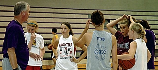 Baldwin High School girls' basketball coach Bob Martin, left, talks to members of his team during camp last week.