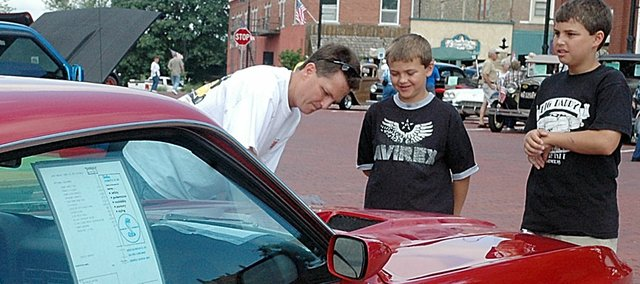 While Rusty Bruns of Baldwin City puts the finishing shine to his 1969 Shelby Cobra Mustang in the Planes, Trains Automobiles car show Saturday, his sons Cameron, 8, and Cody, 13, look on.