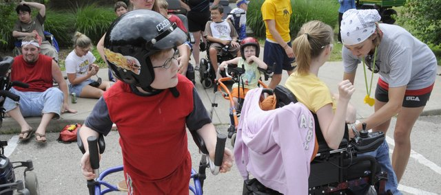 Luke Bruner, 9, Lawrence, center, waits his turn for a ride in a motorcycle sidecar last week at a Muscular Dystrophy Association summer camp at Tall Oaks Conference Center near Linwood. The weeklong camp, solely for kids with degenerative neuromuscular diseases, this year had 69 participants.