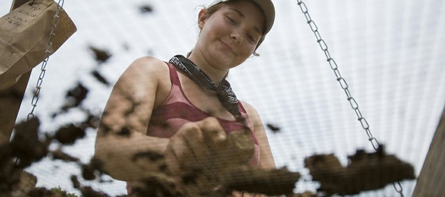 Jess Gisler, a Kansas State University junior from Prairie Village, crushes dirt through a metal mesh in an attempt to find artifacts from an ancient culture.