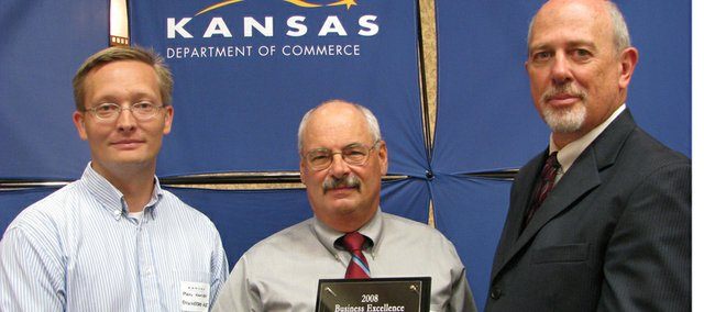 Engineered Air President Ric Rambacher accepts from Kansas Department of Commerce and Housing Secretary David Kerr the KDCH's 2008 east regional's Business Excellence Award for Manufacturing/Distribution. To Rambacher's left is Paul Hansen of Engineered Air.