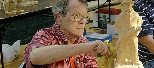 James Hooper of Edmond, Okla., works on a carving of a firefighter Friday during the Kaw Valley Woodcarvers seminar at Baker University's Mabee Memorial Hall.
