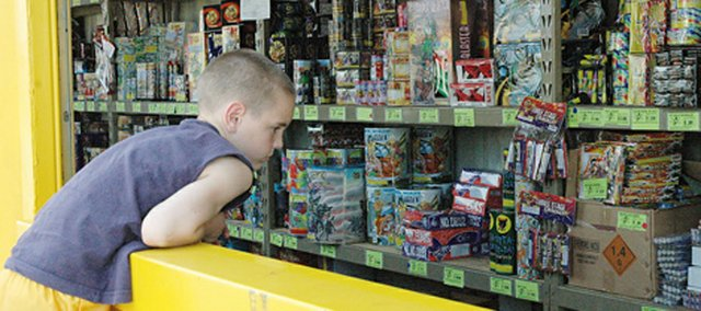 Elijah Hill, Leavenworth, looks over the counter picking out fireworks to buy at the Lunatics Fast-Pitch Softball fireworks stand in Lansing in this 2007 photo.