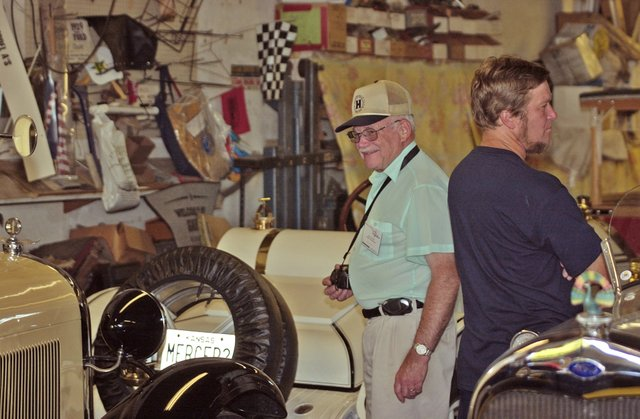 Hupmobile club member Walt Colton smiles at what he sees in Dean Weller's garage. He was part of club of Hupmobile fans having a convention in Topeka this week. They visited De Soto to tour Dean Weller's garage.
