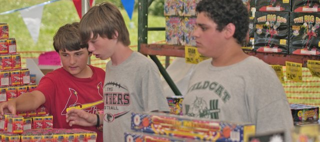 DHS Wildcat freshmen-to-be football players (from the left) Josh McCarthy, Daniel Williams and Devin Barrett stack fireworks Tuesday at the team fireworks stand. It is one of three open in De Soto this year.