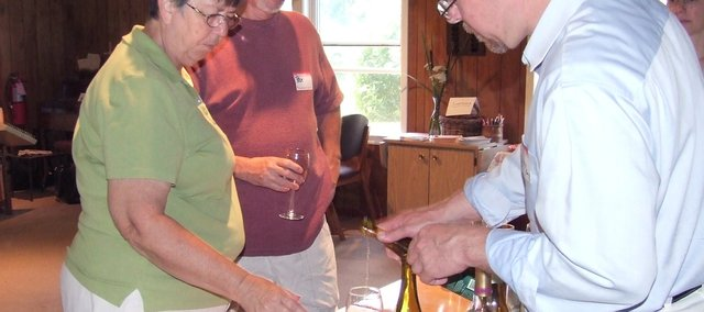 Valorie and Rick Bratcher, left, of Kansas City, listen to Greg West, right, give information about a sample of wine Sunday during the center's wine tasting event. The event was a thank-you to contributors of the center's campaign to raise money for facility additions to the center's grounds.