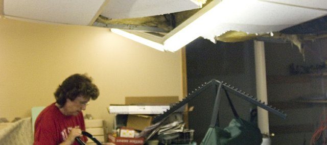 Sylvia Kessinger tries to rescue as many items as she can from the back of her office. Sometime before 10 a.m. Thursday, the southwest corner of the Kessinger Real Estate roof began to cave in. Kessinger believes water began to build up on her roof, which caused the roof to buckle.