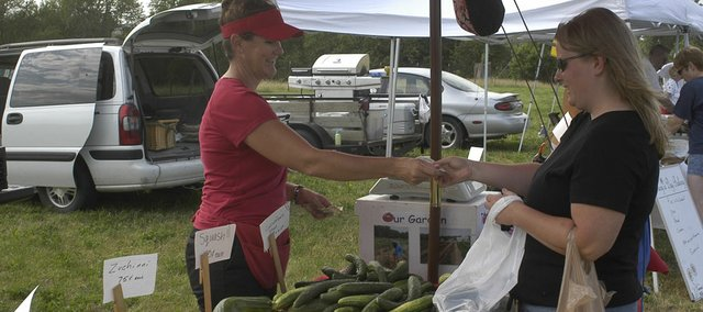 Jane Wohletz, Lawrence, makes change for former De Soto resident Deborah Gulley Wednesday at the Fresh Promises Farmers Market at Zimmerman's Kill Creek Farm in De Soto. It was the first day of the market's season, which is open from 5 to 7 p.m. every Wednesday through September at 9210 Kill Creek Road.