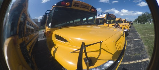 School buses are reflected in a sideveiw mirror in the Tonganoxie High School parking lot. Buses are the only school vehicles driven home by Tonganoxie School District employees.