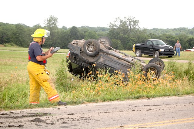 A member of the Stranger Township Volunteer Fire Department surveys the scene of a one-passenger, single-vehicle rollover accident Tuesday afternoon, July 8 on westbound 207th Street, north of Tonganoxie.