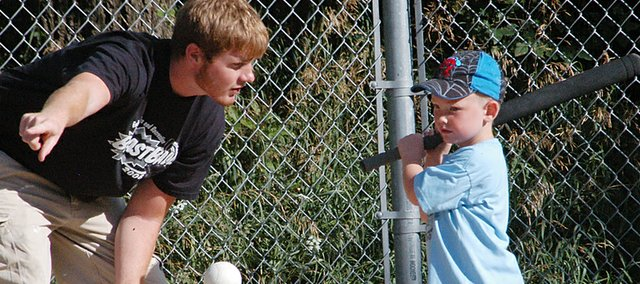 Umpire Zane Pittman offers instruction to Christian Cox, 3, Monday in the opening games of Eudora's blastball league. Eudora Parks and Rec introduced blastball to the community in an effort to teach young girls and boys the basics of baseball and softball.