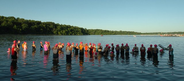 Swimmers wait in the early morning light for the start of the Shawnee Mission Triathlon Sunday.