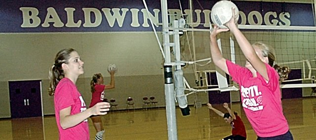 """Baldwin High School junior Katie Brecheisen, left, watches the youth volleyball campers play """"leap frog"""" Friday afternoon during the final day of the camp. Several BHS players helped out at the camp last week after their camp finished."""