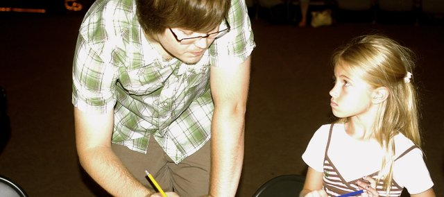 "Wes Wedman helps 7-year-old Ciara Tabor of De Soto sketch the frame of a character Friday at the De Soto Library's ""Drawing Manga"" program."