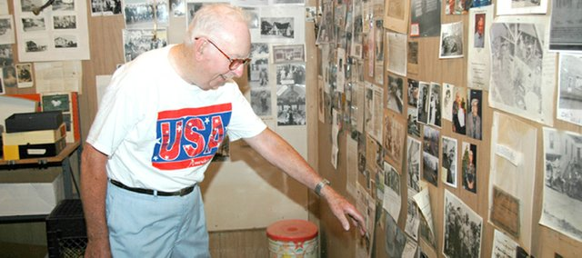 "Tonganoxie resident John Lenahan points out a newspaper clipping in his garage on Washington Street in Tonganoxie. Lenahan, who has written three books about Tonganoxie history, also built a ""museum"" in his garage of clippings and photos from years gone by."