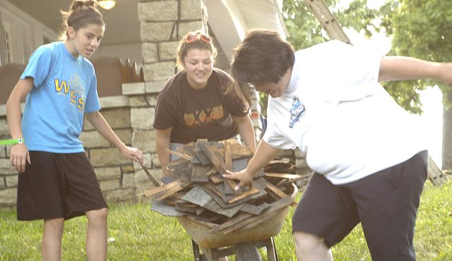 Adrienne Chambers, 12, and mother Alicia Chambers help keep the old shingles in the wheelbarrow Katie Wynn, 18, is pushing to the dumpster. They were part of a youth group from Southside Community Church in Paragould, Ark., that helped repair the roof at De Soto Youth Ministries for a missions trip.