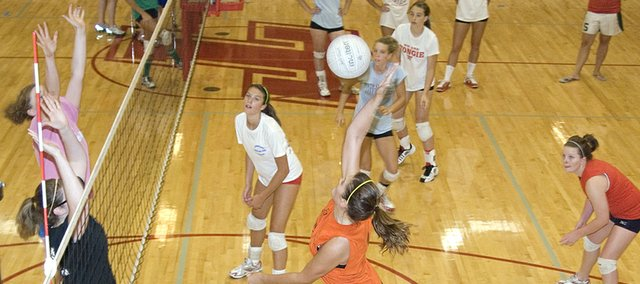 Megan Puhr (center) elevates for a spike at Tonganoxie High volleyball camp. THS players used the four-day camp as a chance to showcase their skills before the upcoming season.
