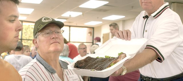 John Hills, Olathe, and Kevin Johnson, Overland Park, judge ribs shown by table official Mike Fracul, Shawnee, for appearance Saturday at the Kansas City Barbecue Society barbecue judging class at the Shawnee Civic Centre.