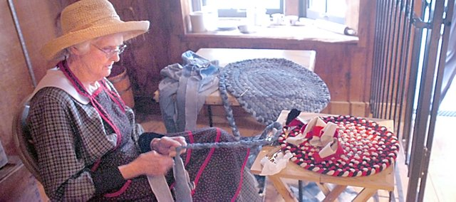 Practicing her hand on a denim braid rug, Joan Russell (left) sits in the General Store during Shawnee Town's Straw Hat Saturdays on July 12. Costumed interpreters demonstrat butter churning and other oldtime farm chores during the Straw Hat Saturdays at Shawnee Town Museum.